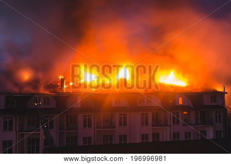 Building in fire at the night burning fire flame with smoke on the apartment house roof.