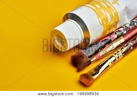 Vintage Artists Brushes With Yube Paint On An Yellow Background.closeup.copy Space