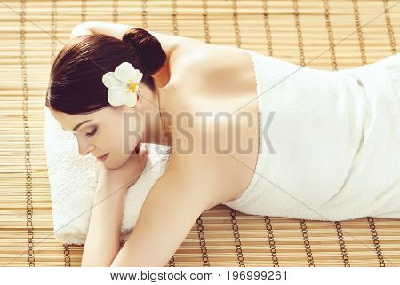 Healthy and beautiful girl getting spa treatment. Woman in spa salon over bamboo mat. Healing and oriental therapy concept.