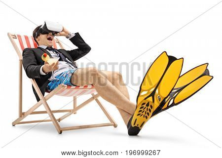 Businessman with swimming fins and a cocktail sitting in a deck chair and using a VR headset isolated on white background