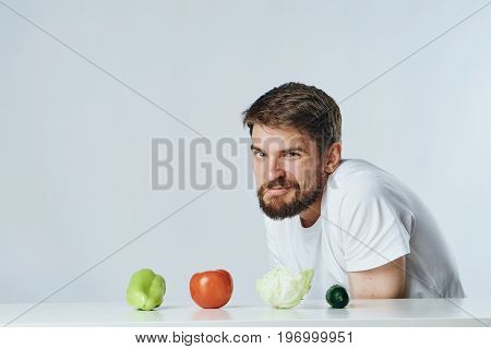 Man with a beard on a white isolated background sits at a table and looks at vegetables, diet, vegetarianism, vegetarian.