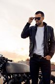 Closeup of a handsome rider guy with beard and mustache in black biker jacket take off fashion sunglasses smoking cigaret near classic style cafe racer motorbike at sunset. Brutal fun urban lifestyle. poster
