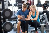 Smiling personal trainer using digital tablet while talking to blonde woman at gym. Happy couple using tablet in fitness club. Client trainer looking at computer her progress at the gym. poster
