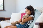 Smiling young girl sitting on couch and embracing her teddy bear. Asian cute little girl hugging stuffed toy at home. Multiethnic female child playing with plush toy bear on the sofa. poster