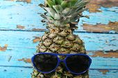 Pineapple fruit with blue  sunglasses/ Pineapple fruit with blue  sunglasses in front of scraped blue planks. poster