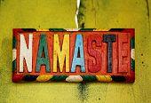 Colorful sign NAMASTE - the Sanskrit salutation - on old rustic wall poster