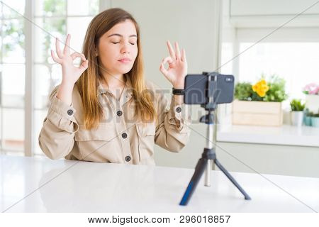 Beautiful young woman doing online video call using smartphone webcam relax and smiling with eyes closed doing meditation gesture with fingers. Yoga concept. poster