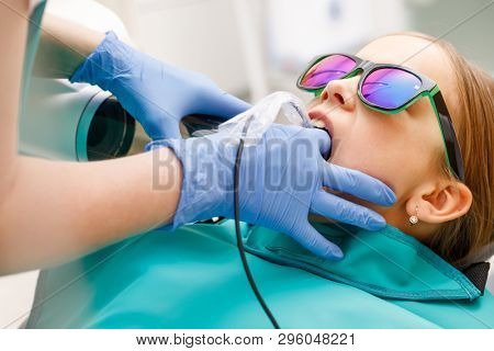 Radiographer taking teeth radiography to a girl using digital x-ray machine in pediatric dental clinic. Doctor pointing X-ray unit  holding electronic sensor in child's open mouth performing scanning