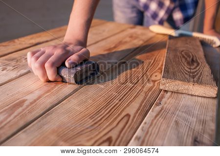 Hand with snad paper sanding center piece of a vintage wooden table, Woodworker, carpenter working concept