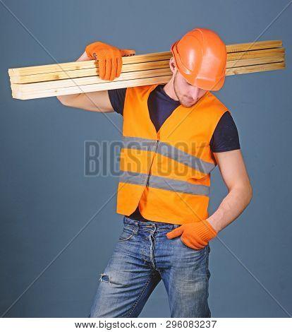 Hardy Labourer Concept. Man In Helmet, Hard Hat And Protective Gloves Holds Wooden Beam, Grey Backgr