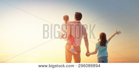 Happy loving family. Father and his daughters children playing and hugging outdoors. Cute little girls and daddy.