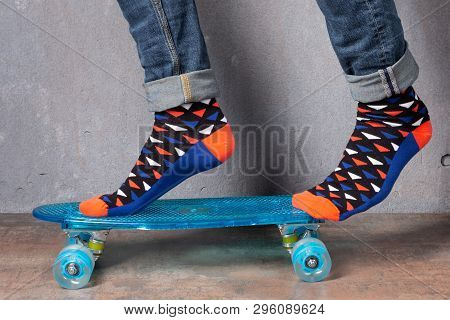 Mens Legs In Colored Socks, On A Blue Skateboard, Socks Concept And Lifestyle, Against A Grunge Wall