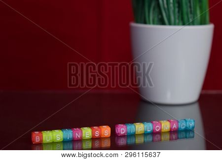 Business Diplomacy Text At Colorful Wooden Block On Red Background. Desk Office And Education Concep