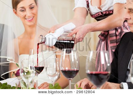 Wedding party at dinner - wine is be poured into glasses