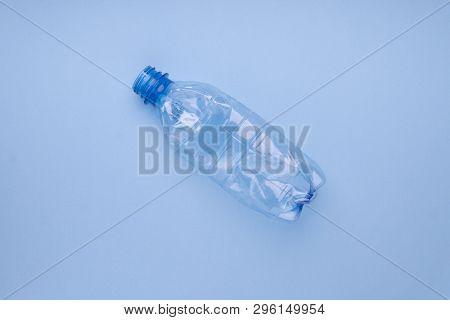 Squashed plastic bottle on vivid bright blue background. Plastic utilisation concept. Ecological problem, global environment.