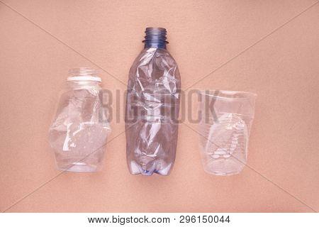 Squashed plastic bottles and a cup on beige tan orange background. Plastic utilisation concept. Ecological problem, global environment.