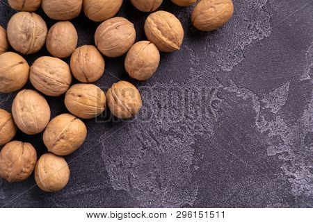 Bunch of whole walnuts on dark blue slate background. Healthy diet composition, background