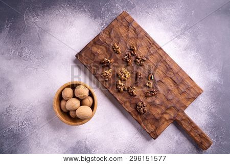 Walnuts in wooden bowl on wooden carved board, top view. Healthy nuts and seeds composition.