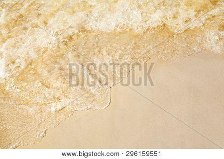 Sand on the beach, splashing waves on the seashore.
