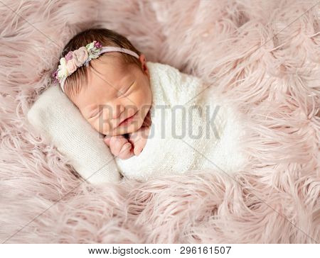 Little cutie infant girl sleeping on baby bed