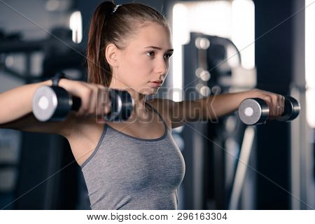 Attractive Young Sports Woman Lifting Dumbbells in the Gym. Fitness and Healthy Lifestyle Concept.