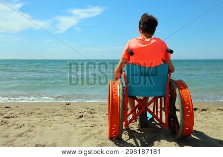 Young Boy On The Wheelchair By The Sea During The Summer Vacations