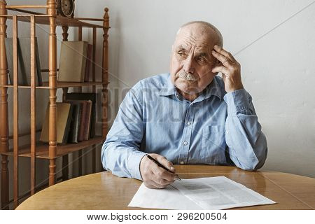 Worried Elderly Man Completing A Form Seated At The Table With His Hand To His Head Looking Aside Wi