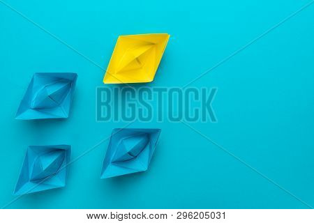 Conceptual Image Of Leadership With Yellow Paper Ship On Blue Background. Top View Of Leadership Con