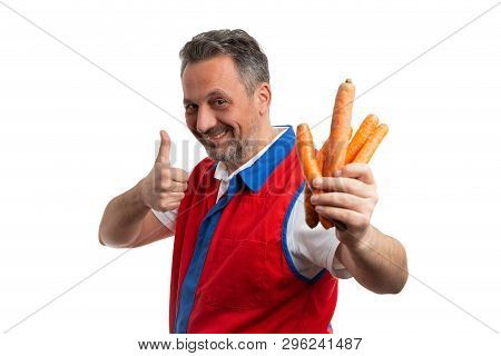 Trustworthy grocery store or hypermarket male employee making like gesture with thumb up as presenting carrots isolated on white poster