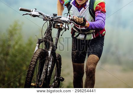 Dirty Cyclist Climbing Uphill With Mountain Bike On Foot