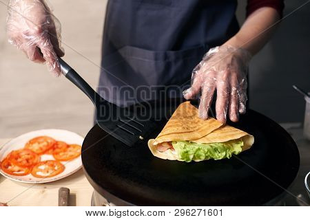 Chef In Gloves Making Crepe On Hot Round Portable Cooktop. Skillful Hands With Spatula In Final Stag
