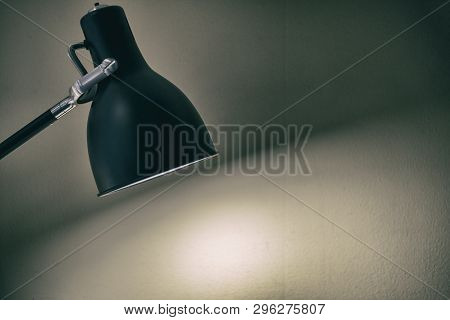 Black fixture lamp with white  wall background poster