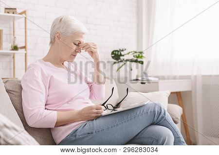Eye Strain Problem. Upset Senior Woman Taking Off Glasses, Suffering From Blurry Vision After Long U