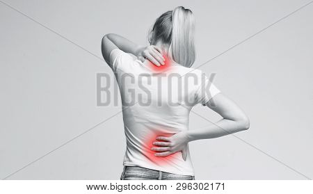 Woman With Neck And Back Pain, Rubbing Her Painful Body, Back View, Panorama