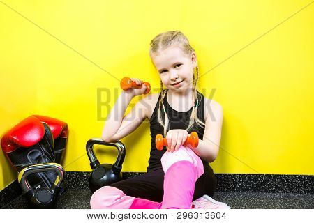 Theme sports and health children. Little funny child Caucasian girl with pigtails, sits resting break on floor in gym. Athlete dumbbell equipments for gymnastics bodybuilding background yellow wall poster