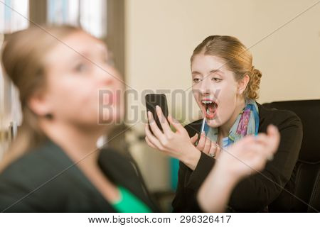 Pretty Young Woman Applying Lip Gloss At Her Desk