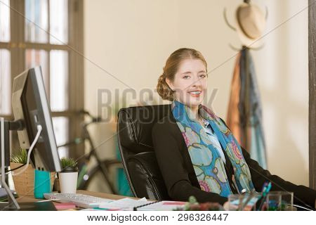 Happy Young Professional Woman With Braces Sitting At Her Desk