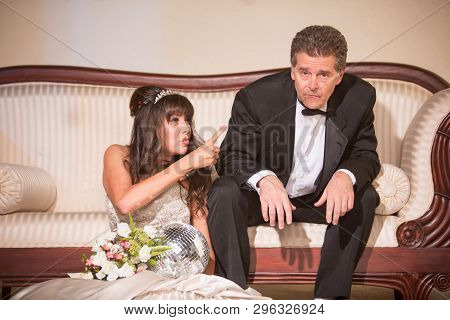 Upset Bride Sitting On The Floor Pointing At New Husband