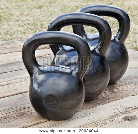 three black iron kettlebell for weight training (35 and 50 lb) on wood grunge deck outdoors with sky reflections poster