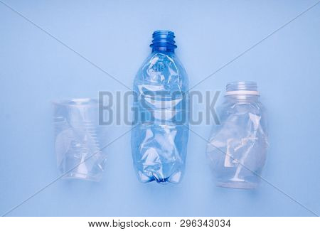 Squashed plastic bottles and a cup on bright blue background. Plastic utilisation concept. Ecological problem, global environment.