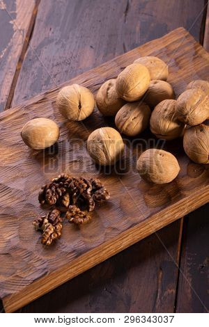 Bunch of walnuts on carved wooden board, wooden background. Healthy nuts and seeds composition, background.