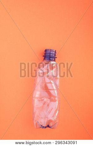 Squashed plastic bottle on orange background. Plastic utilisation concept. Ecological problem, global environment.
