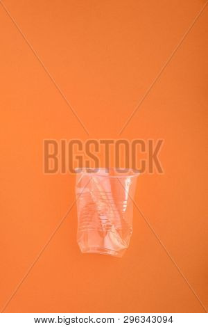 Squashed plastic cup on orange background. Plastic utilisation concept. Ecological problem, global environment.