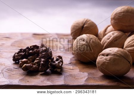 Whole walnuts lying on carved wooden board, side view. Healthy nuts and seeds composition, background.