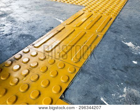 Yellow Dome And Block Of Tactile Paving Which Act As A Guidance For Visually Impaired Or Blind Citiz