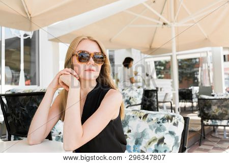 portrait of real young woman sitting in a Coffee Shop.