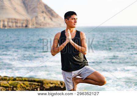 Young Man Doing Yoga And Meditating In Tree Position At Sea Beach. Vrikshasana