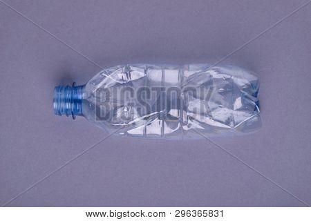 Squashed plastic bottle on gray background. Plastic utilisation concept. Ecological problem, global environment.