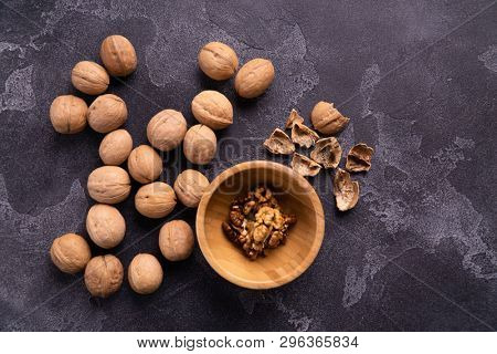 Cracked walnuts in wooden bowl and on black slate surface. Healthy nuts and seeds composition.