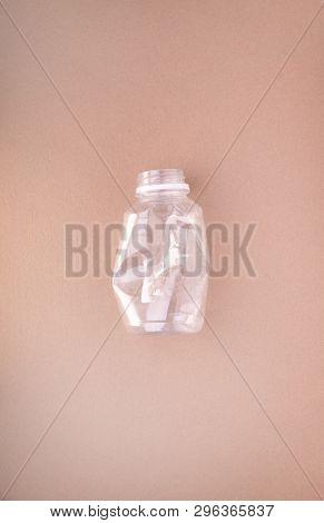 Squashed plastic bottle on beige tan background. Plastic utilisation concept. Ecological problem, global environment.